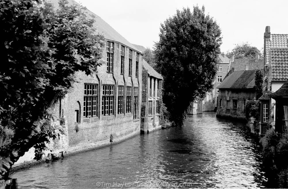 A canal in old Bruges snakes between historic medieval buildings.