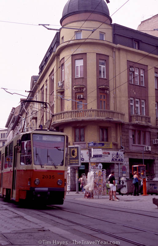 A streetcar rumbles past a worn building in Bulgaria's capital of Sophia.