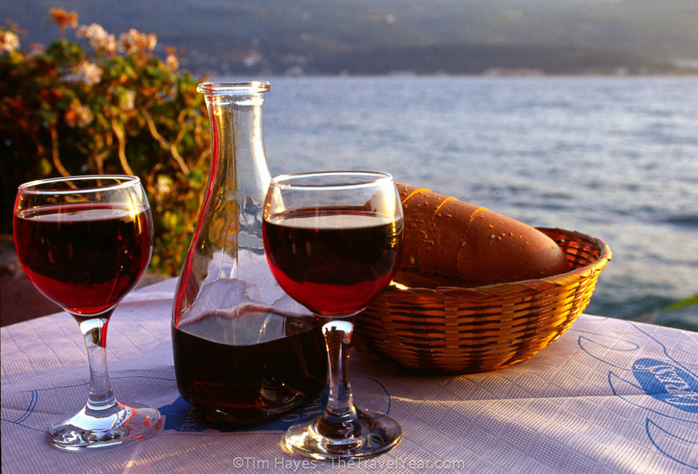 A typical start to dinner in a Greek restaurant - a paper tablecloth, a carafe of inexpensive red wine, a load of bread, and a view of the sea.