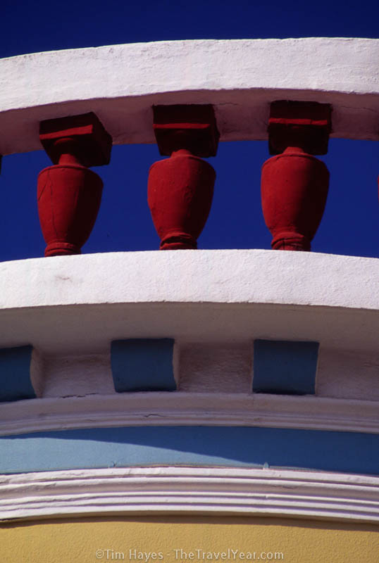 Red pillars adorn the rooftop of a colorful building on the Greek island of Samos.