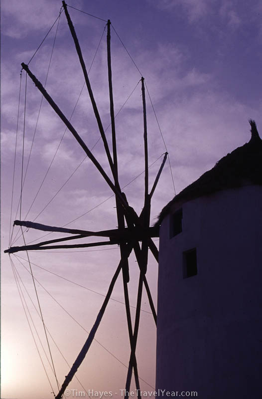 Sun sets behind a windmill on the picturesque town of Ia, located in the Greek Cyclades island of Santorini.