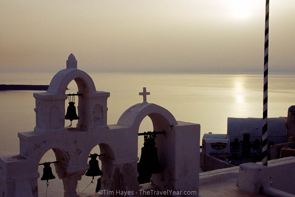 The sun sets beyond a chuch on the picturesque town of Ia, located in the Greek Cyclades island of Santorini.