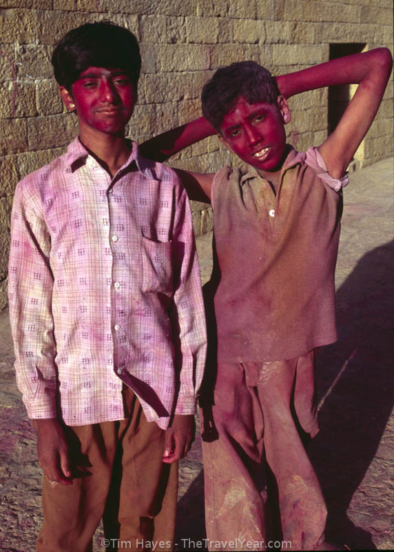 Two children, participants of Holi, have been stained red by colored gulal powder in the old section of Jaisalmer. This Hindu festival of color marks the end of winter and commemorates a legend from Hindu mythology.