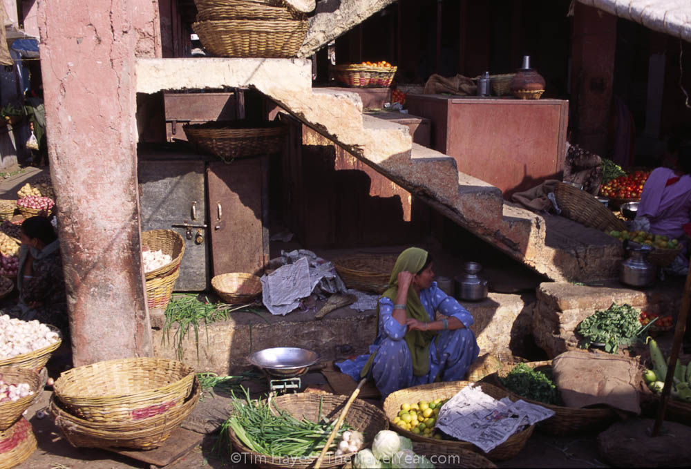 A woman sells vegetables in Udaipur's market.