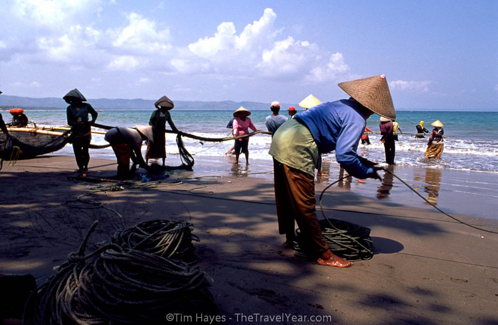 Villagers in Pangandaran, Indonesia, pull a fishing net in from the surf.