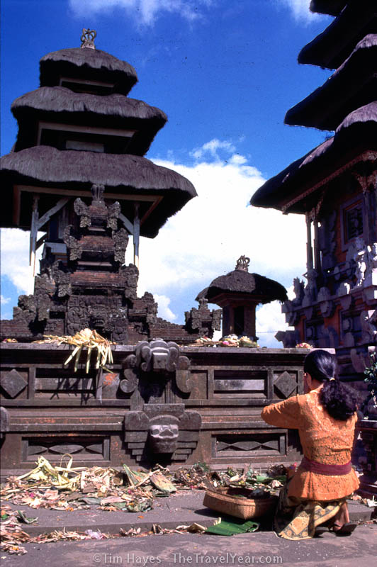 A woman places an offering on the altar of the Kintamani Ulan Dano Hindu temple in Bali. Old offerings cover the altar and the ground surrounding it.