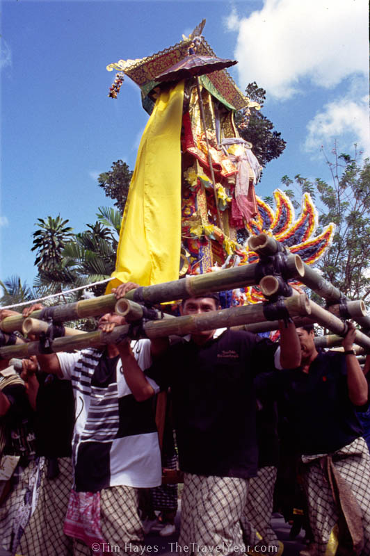 A cremation procession passes by in Ubud, Bali.XXXXThe cremation ceremony is one of the most important rituals in the life of a Balinese Hindu. It takes much time and money to plan and can take place up to years after the person's actual death.XXXXIn the photo here, the body is being carried from a temporary burial ground to the cremation ground in a high tower that can me made of anything including paper, bamboo, string, tinsel, mirrors, silk, cloth, flowers or other colorful items. The large group of men who carry the tower walk down the street in a seemingly drunken manner – zigzagging down the street and spinning the tower in circles. But far from being drunk, these men are trying to confuse the spirits so that they do not return home to cause mischief.