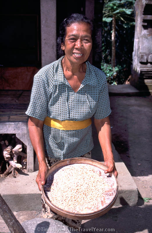 An woman sifts rice near the touristy Elephant Temple in Bali, Indonesia.XXXXI took this photo with her permission, but then she demanded money afterward. I don't like to pay for photos, so I said no and walked away in a hail of curses.  I wonder what she cursed me with?