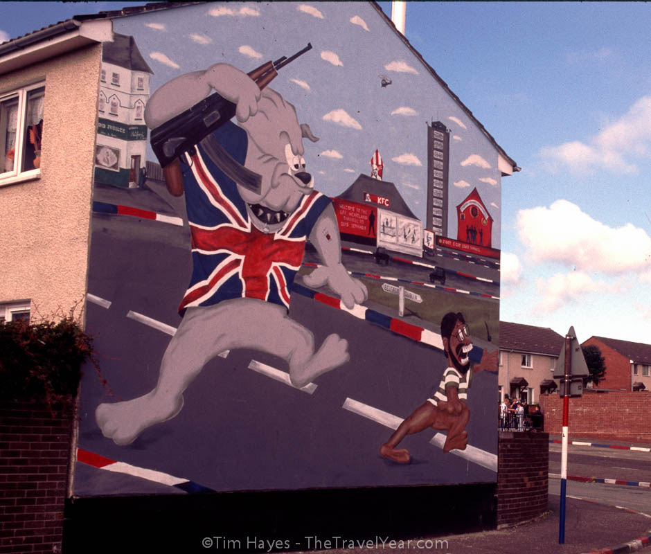 Cartoon mural in Protestant Shankill Road area of Belfast depicting a caricature of Sinn Fein leader, Gerry Adams, being chased back to Dublin by a Loyalist bulldog.