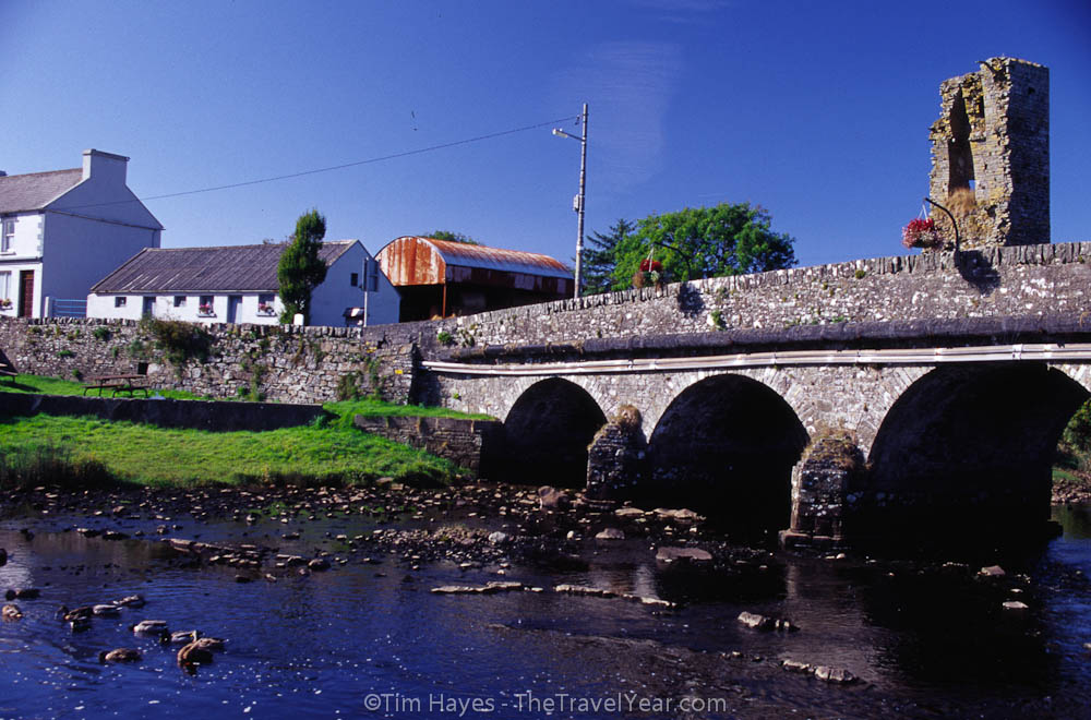 An old stone bridge crosses a stream in the small village of Doonbeg, County Clare.
