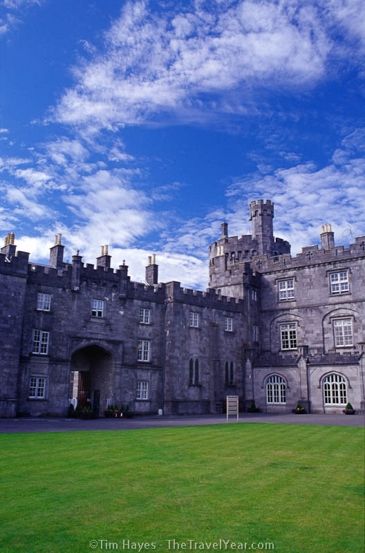 Originally built in the 12th century, Kilkenny Castle is pictured here with an exceptionally green lawn and blue sky.