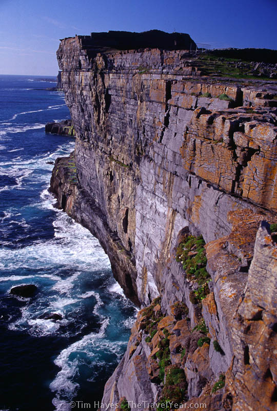 Surf crashes along an 87-meter high cliff of Inishmore Island, County Galway. The view looks out over the 3,000-year-old Dun Aengus ring fort, inhabited from 1100 BC to 1000 AD. (The fort stands on top of the cliff.)