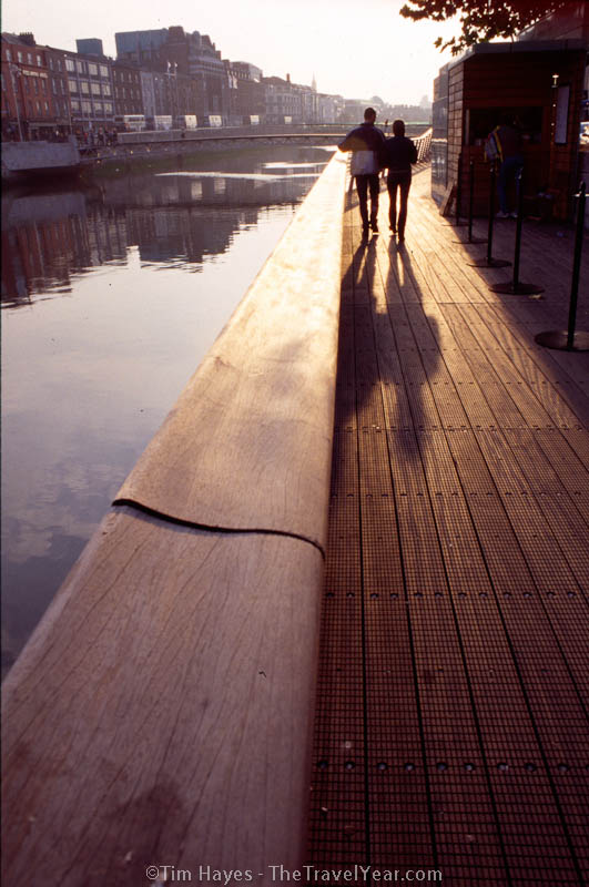 A couple walks adjacent to Dublin's famous River Liffey during sunset.