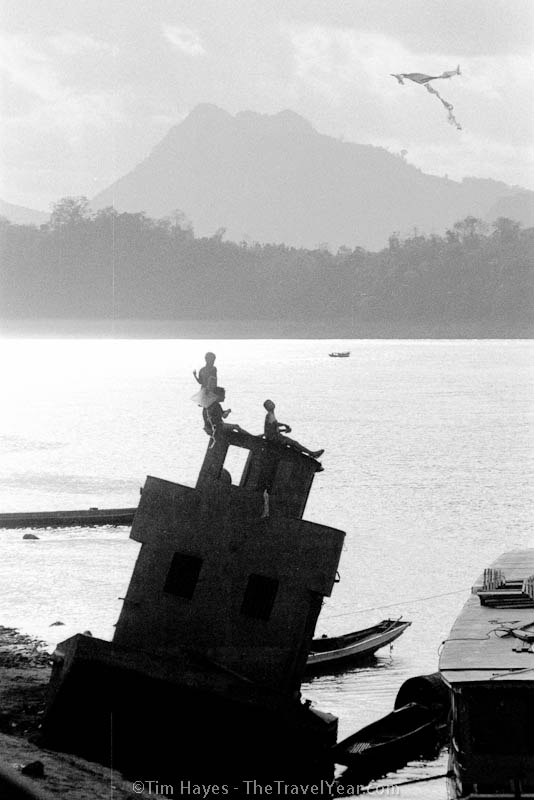 Children fly a kite from the top of an old wrecked boat along the shore of the Mekong River.