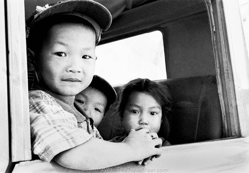 Three Laotian children look curiously out the window of their parents' pickup truck in Luang Prabang, Laos.