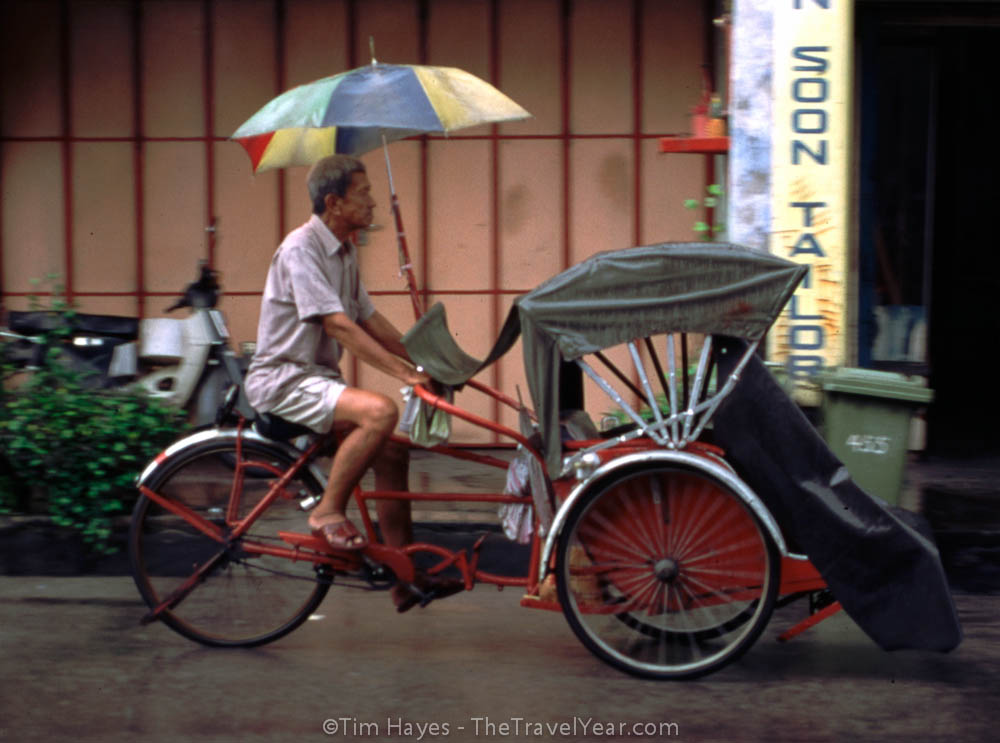 A rickshaw driver pedals down the street in the rain.