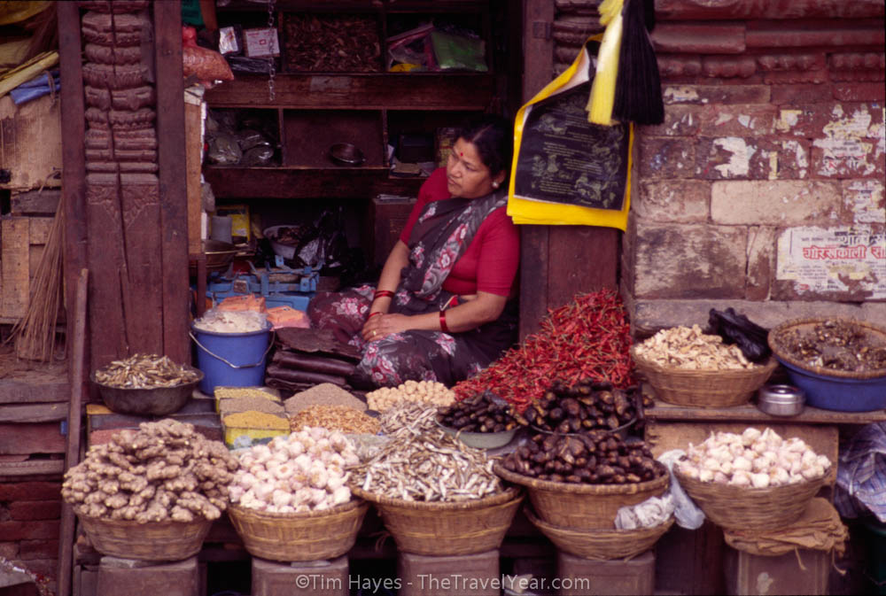 A woman sells dried chilies, garlic, ginger, and other dry goods from a booth in Kathmandu's Durbar Square.