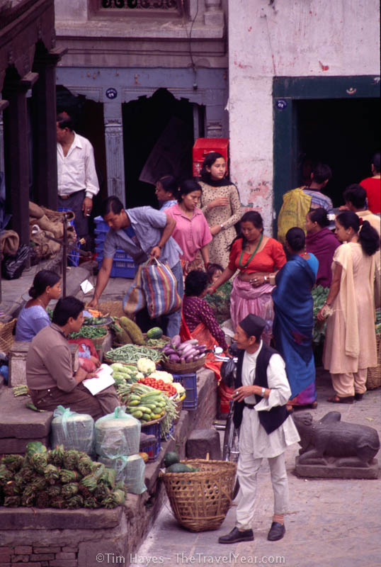 People gather to talk and buy vegetables from a market in Kathmandu's Durbar Square.