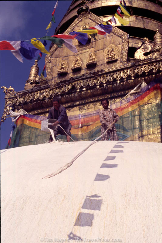 Two men try to keep the stupa at Kathmandu's Monkey Temple (Swayambhunath) brightly whitewashed during an important Buddhist celebration.