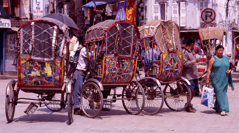 Four rickshaw drivers wait for business on a busy Kathmandu street.