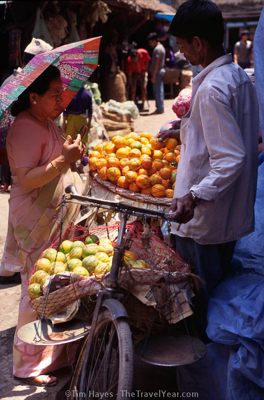 A woman buys oranges from a vender who carts his goods around on his bicycle.