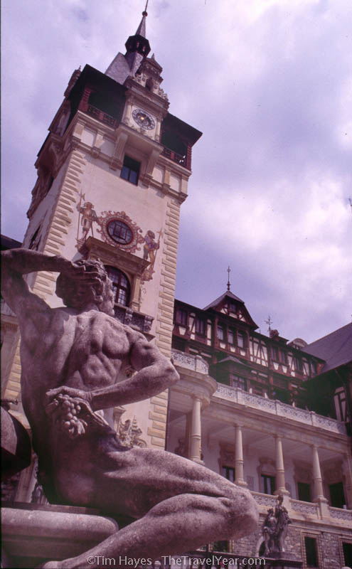 A statue stands out front of the Pelis Castle, the summer residence of German/Romanian King Carol.  Built in the German-Renaissance style between 1875 and 1914.