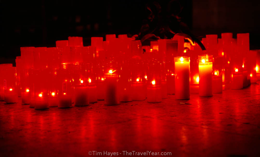 Red church candles offer prayers in a San Sebastian Catholic church.