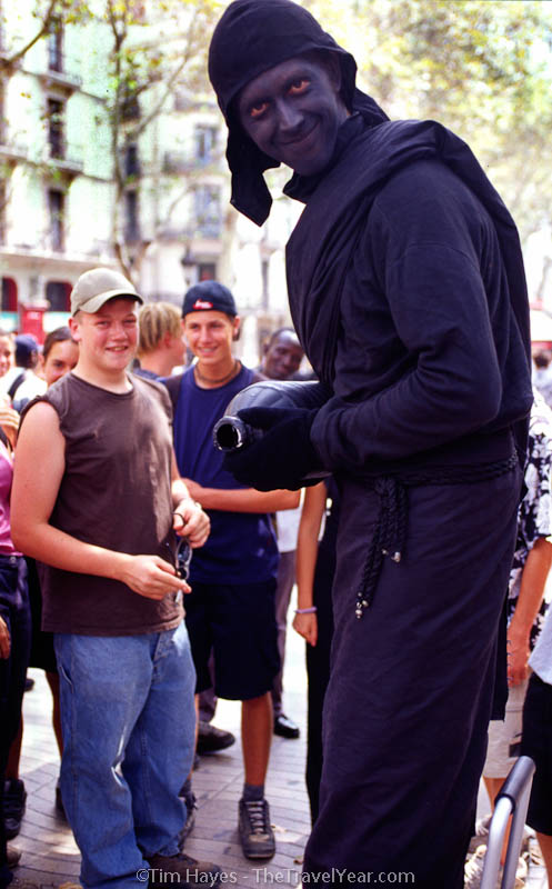 The tree-lined pedestrian area of Barcelona's La Rambla attracts tourists, locals, and street performers such as this human statue. This black bandit stands still until offered a coin, then he turns into a fountain, pouring mysterious liquid into an oil pan below his feet.