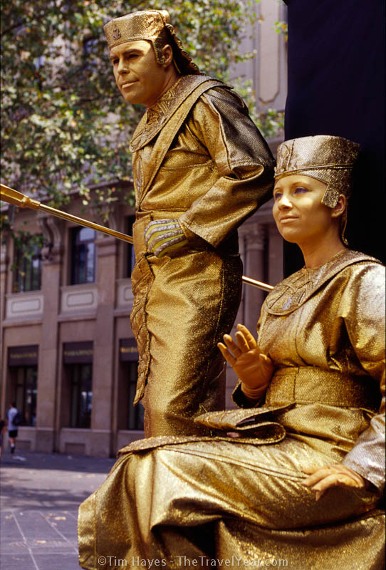 The tree-lined pedestrian area of Barcelona's La Rambla attracts tourists, locals, and street performers such as these human statues. This gold couple stands still until offered a coin, then they move slowly into position for photographs with the kids.