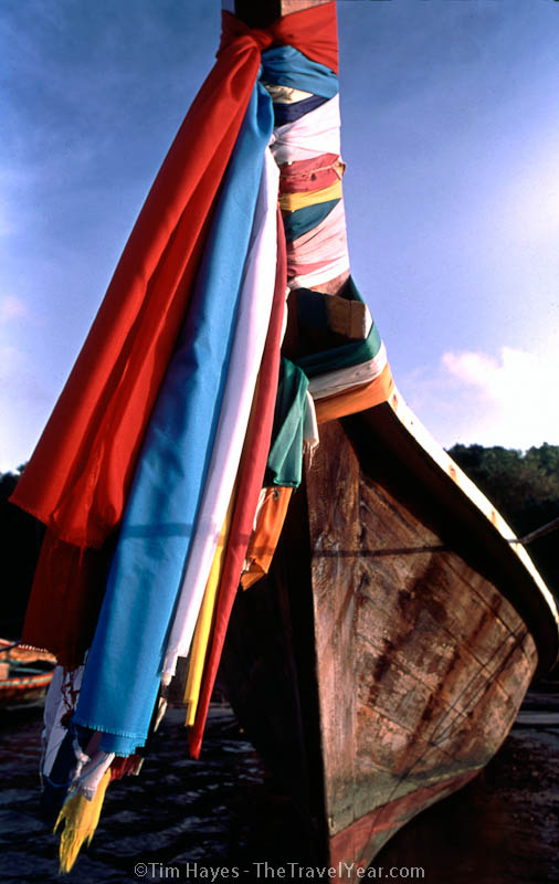 A colorful Thai sea gypsy boat is decorated with streamers that help to keep the sailors safe.
