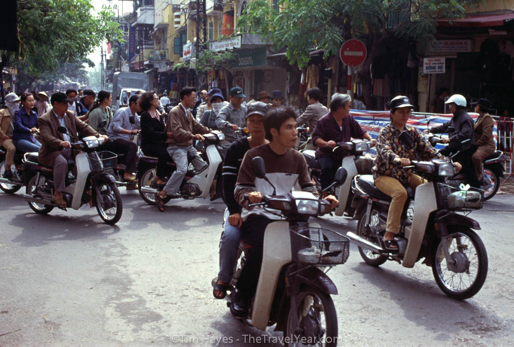 The average intersection in Hanoi, missing any traffic controls, promotes a controlled anarchy unique to Vietnam. Motorcycles converge on this intersection from all sides, mix around as if in a blender, and pop out on the other side unharmed.
